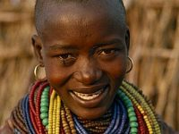 UGANDA  Karamoja District Portrait of Karamojong woman wearing multiple coloured bead necklaces.  Her hair style indicates her clan.  Colored